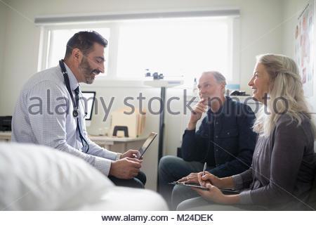 Médecin homme with digital tablet talking to senior couple patient en salle d'examen Banque D'Images
