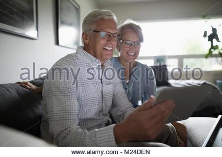 Chat vidéo Happy senior couple with digital tablet sur salon canapé Banque D'Images