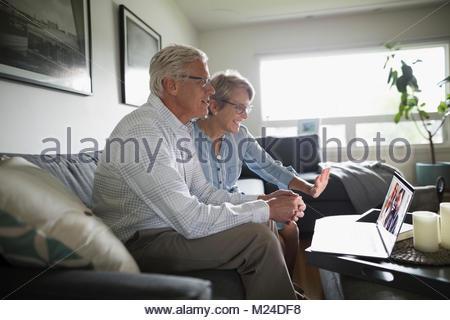 Senior couple forme, le chat vidéo avec ordinateur portable sur salon canapé Banque D'Images
