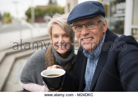 Portrait of smiling senior couple drinking coffee at sidewalk cafe Banque D'Images