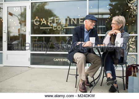 Senior couple drinking coffee and talking at sidewalk cafe Banque D'Images