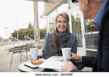 Smiling senior couple drinking coffee at sidewalk cafe Banque D'Images