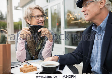 Senior couple talking and drinking coffee at sidewalk cafe Banque D'Images