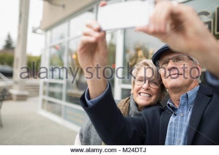 Smiling woman with camera phone selfies at sidewalk cafe Banque D'Images