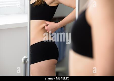 La réflexion d'une femme de pincer la peau du ventre dans le miroir Banque D'Images