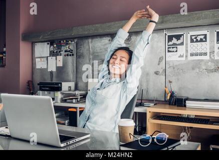 Creative designer asiatique soulever jusqu'à bras et le près en face de l'ordinateur portable sur le bureau,se détendre Banque D'Images
