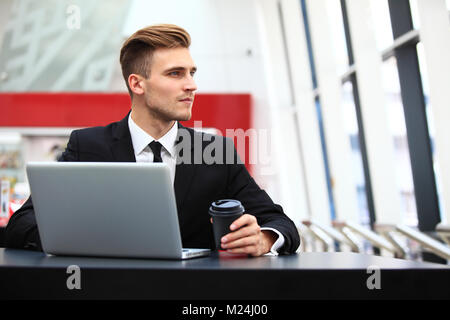 Young adult using laptop in airport lounge Banque D'Images