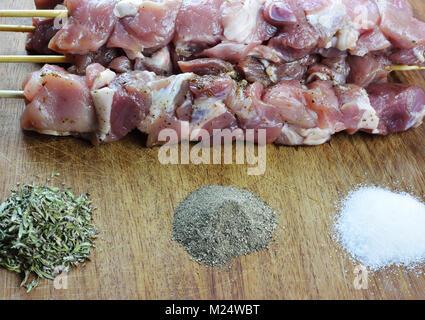 Souvlaki brut avec des épices sur une planche en bois Banque D'Images