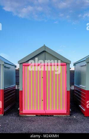 Brighton Beach Hut avec une porte de couleur jaune, rose, rayures noires derrière est bleu ciel et infront est la Banque D'Images