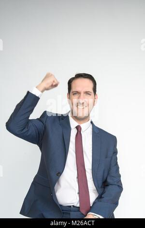 Portrait d'un bon habillés à l'homme en souriant et heureux à la caméra et dans l'air frappe avec joie. Isolé sur fond blanc