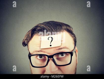 Jeune homme à lunettes avoir question à l'esprit à la perplexité. Banque D'Images