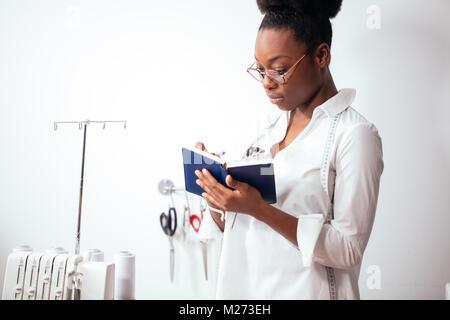 Jeune fille africaine couturière prendre des notes à l'ordinateur portable. designer croquis dessin Banque D'Images
