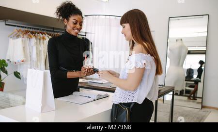 Concepteur commercial client porter lors d'une boutique de mode. Le paiement du client en utilisant une carte de Banque D'Images