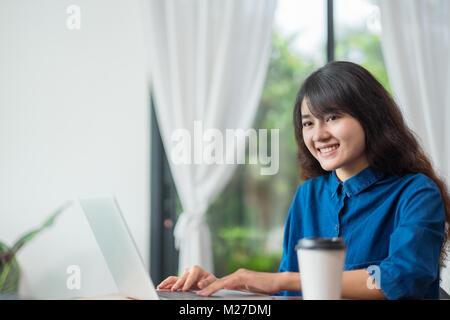 Asian woman using laptop computer près de fenêtre à cafe restaurant,mode de vie,à l'aide d'âge numérique Technolgy Banque D'Images