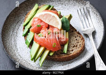 Sandwich au saumon fumé et d'avocat sur la plaque. Selective focus Banque D'Images