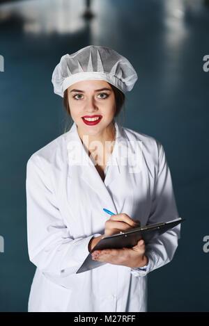 Girl scientifique ou un travailleur dans l'uniforme blanc prend des notes sur papier dans le contexte de la modernisation Banque D'Images
