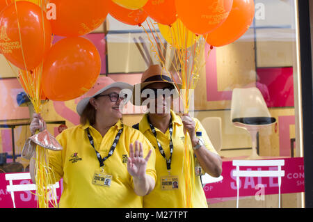 Deux volontaires smiling in chemises jaunes holding orange de ballons à l'été Fayre Marlyebone Marlyebone Food Festival Banque D'Images