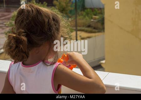 Petite fille blonde avec les cheveux bouclés Playing with toy de prismatique le toit d'une maison sur une journée ensoleillée.