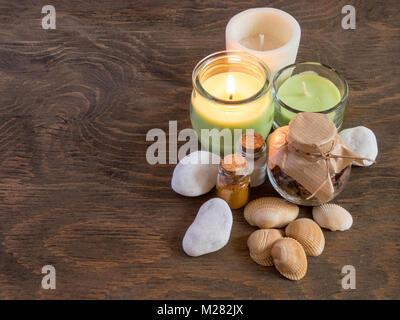 Set d'épices et ingrédients pour l'aromathérapie et soins du corps sur la surface en bois. bougie brûlante flamme. Banque D'Images