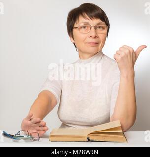 Femme de la nouvelles lunettes montre un signe qu'elle se porte bien et pousse vieux verres et d'une loupe Banque D'Images