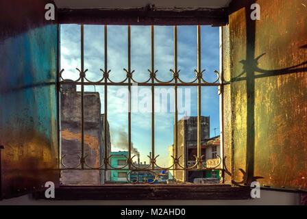 Ouvrez les volets de contreplaqué peint avec peinture brun huile fenêtre avec grille en métal ajouré. Dans l'arrière Banque D'Images