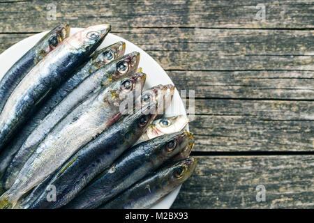 Sardines crues poisson sur la plaque. Vue d'en haut. Banque D'Images
