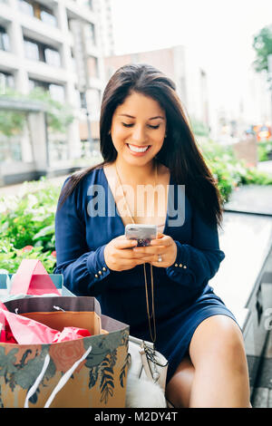 Hispanic woman with shopping bags sitting on bench texting on cell phone Banque D'Images