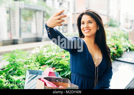 Hispanic woman sitting on bench posant pour selfies téléphone cellulaire Banque D'Images