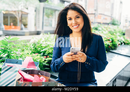 Portrait of smiling Hispanic woman with shopping bags texting on cell phone Banque D'Images