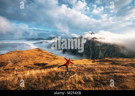 Jeune homme randonneur en veste rouge se tient dos à la caméra comme l'oiseau en vol ou en avion sur une falaise Banque D'Images