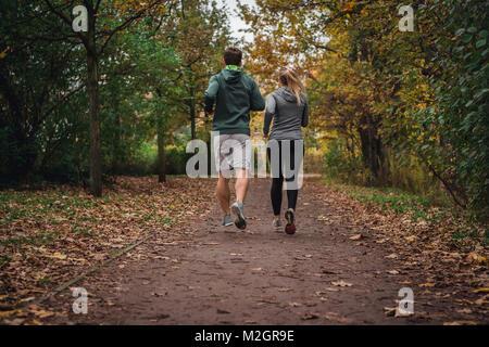 L'homme et de la femme de race blanche qui traverse le parc en automne automne en bas une piste vide. Banque D'Images