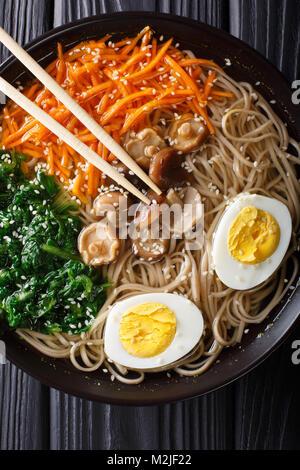Nouilles Soba soupe avec des légumes, des champignons shiitake, des oeufs et de close-up de sésame dans un bol. Banque D'Images