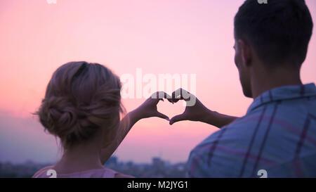 Amants leur main ensemble en forme de coeur, démontrant leur amour Banque D'Images