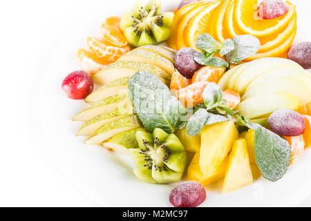 Plateau à fruits, isolé. Apple, mandarine, kiwi, raisin, menthe, poire, pomme, ananas. Salade de fruits dans la Banque D'Images