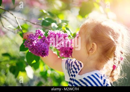 47312d0a31b55 ... Petit enfant qui sent les tulipes sur la fleur lit dans un beau jour de  printemps
