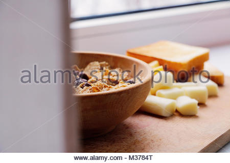 Du fromage, des toasts et des céréales au hasard sur la coupe de bois Banque D'Images