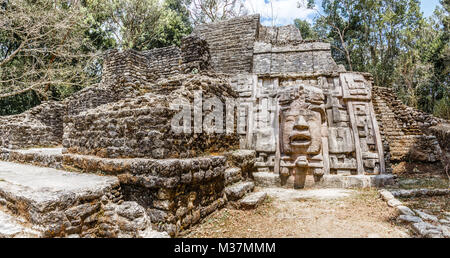 Ancienne en pierre ancienne civilisation précolombienne Maya pyramide avec visage sculpté et de l'ornement caché dans la forêt, site archéologique de Lamanai, Orange Walk