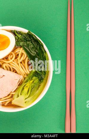 Bol de nouilles ramen de porc style Japonais soupe avec Pak choi et un Œuf dur sur un fond vert