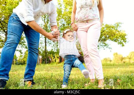 Les premiers pas du bébé. Les parents enseignent à leurs enfants à Banque D'Images