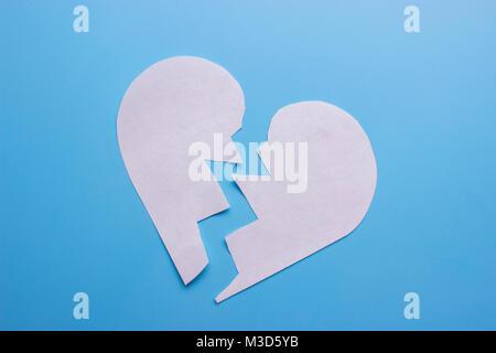 Cœur brisé sur fond bleu. liquidation concept Banque D'Images