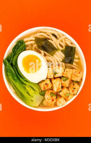 De style japonais, Tofu soupe végétarienne aux nouilles Ramen ou le bouillon sur un fond rouge Banque D'Images