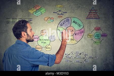 Jeune homme concentré s'appuyant sur la création de tableau et plan d'affaires. Banque D'Images
