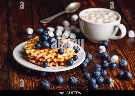 Gaufres Belges sur la plaque avec de bleuets frais et une tasse de chocolat chaud avec de la guimauve. Cuillère Banque D'Images