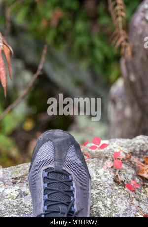 Libre d'une randonnée ou l'escalade chaussure debout sur un rocher à la recherche vers le bas ci-dessous Banque D'Images