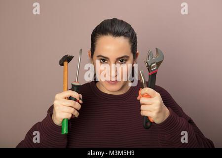 Capable Jeune femme tenant un ensemble d'outils dans ses mains dans un concept de bricolage, de réparation et de Banque D'Images
