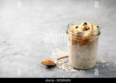 Régime alimentaire sain petit déjeuner. Du jour au lendemain avec l'avoine, les graines de chia bananes, beurre Banque D'Images