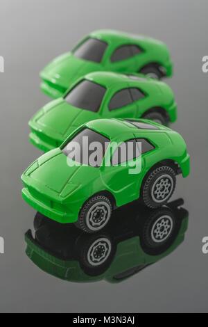 Trois voitures jouets vert sur fond réfléchissant. Métaphore Green cars, les véhicules Tesla, empreinte carbone, Banque D'Images