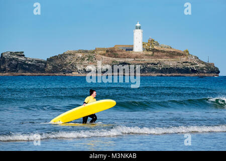 Jeune femme à surfer carrying surf mer conseil à godrevy, Cornwall, Angleterre, Grande-Bretagne, Royaume-Uni. Banque D'Images