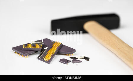 Processeur d'ordinateur cassé sur l'arrière-plan flou avec un marteau. Des fragments de l'unité centrale de traitement. Banque D'Images