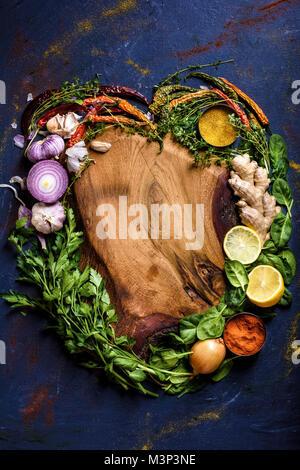 Vue de dessus du cœur fait à partir d'herbes, de légumes et d'épices et planche à découper en bois sur bleu Banque D'Images